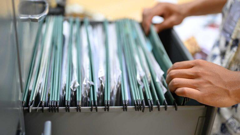 A person rifling through an open filing cabinet